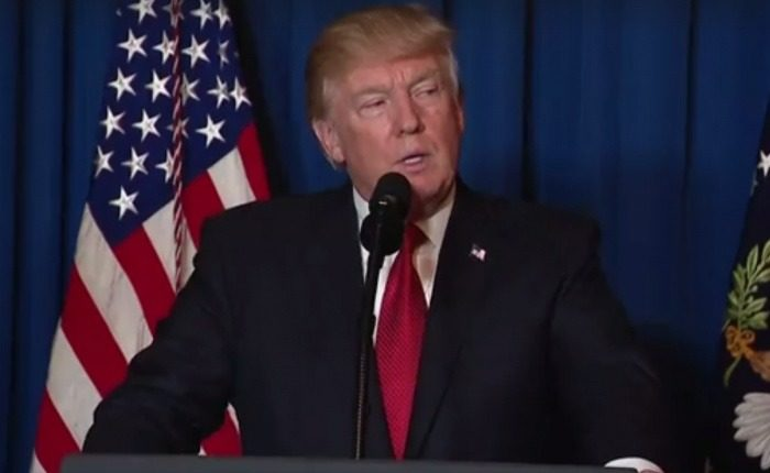 La président américain Donald Trump, au micro devant un drapeau des Etats-Unis