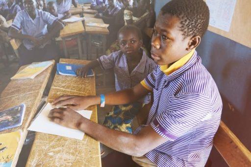 Des écoliers africains en uniforme en train de lire en braille