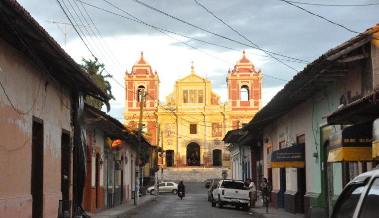 Rue déserte débouchant sur l'imposante Eglise de Leon illuminée par la lumière du soleil couchant