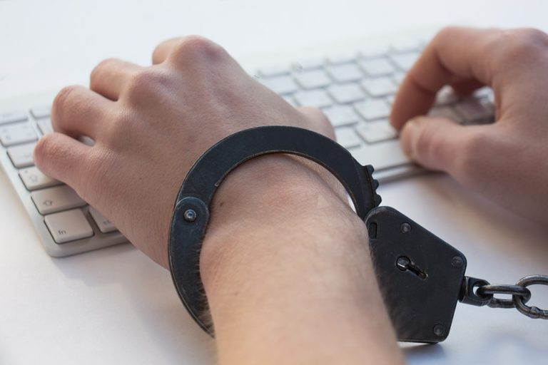 L'image représente des mains enchaînées par des menottes sur un clavier d'ordinateur. Elle symbolise l'addiction et dans ce cas particulier l'addiction à des contenus à caractère pédophile.