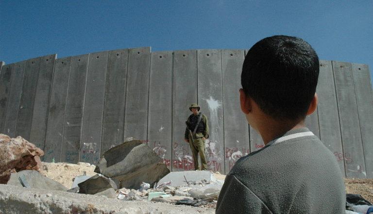 Un garçon palestinien et un soldat israélien devant la barrière israélienne de Cisjordanie.