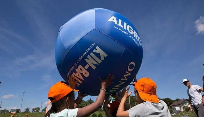 des enfants sont en train de soulever à trois un ballon géant au-dessus de leur tête