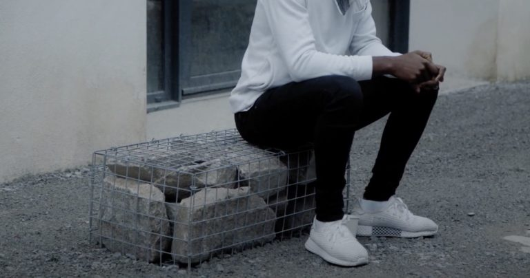 Un adolescent noir assis sur un tas de pierre. On ne voit pas son visage. Il porte un haute blanc, un pantalon noir et des baskets blanches