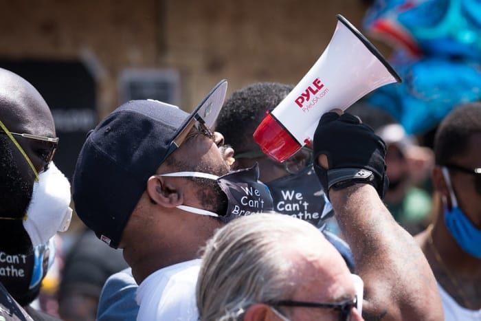 Terrence Floyd tient un mégaphone dans sa main gantée de noir. Au milieu d'une foule, il porte une casquette et un masque sanitaire à moitié rabattu sur son menton
