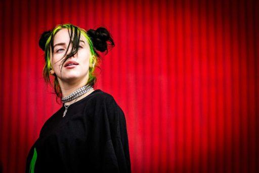 La chanteuse Billie Eilish, habillée de noir devant un fond rouge