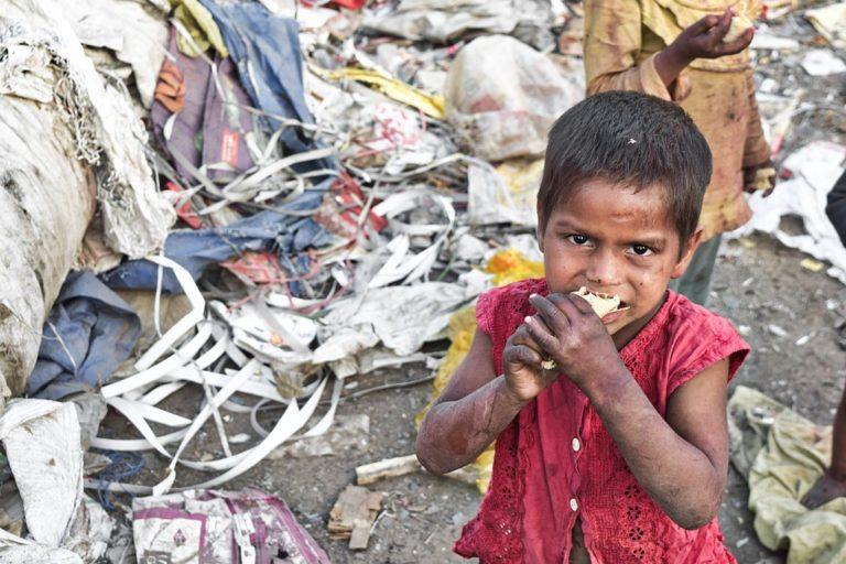 Un enfant dans un bidonville d'Asie mange le peu de nourriture qu'il trouve au milieu des détritus.