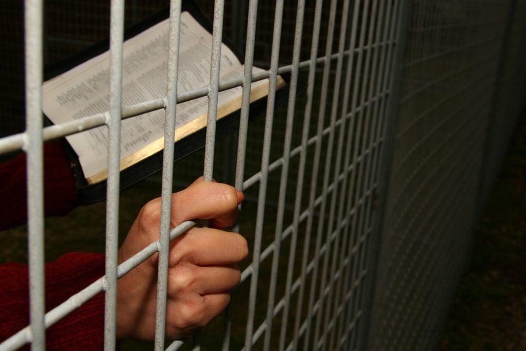 Un prisonnier lit sa Bible à travers les barreaux