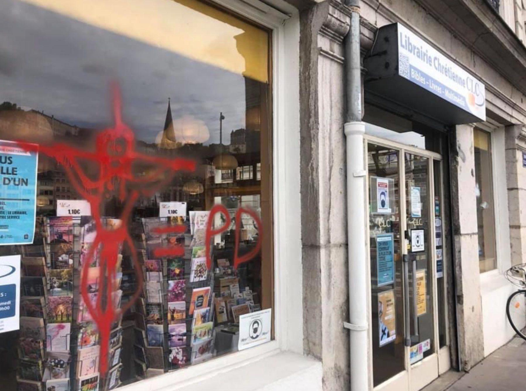 vitrine d'une librairie chrétienne taguée d un christ en croix suivi d une insulte