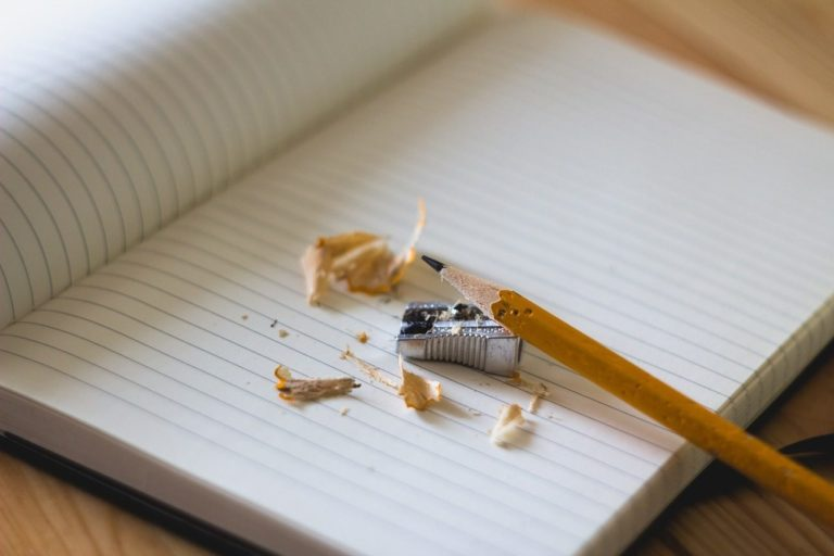 Un cahier ouvert avec un crayon de papier et un taille crayon