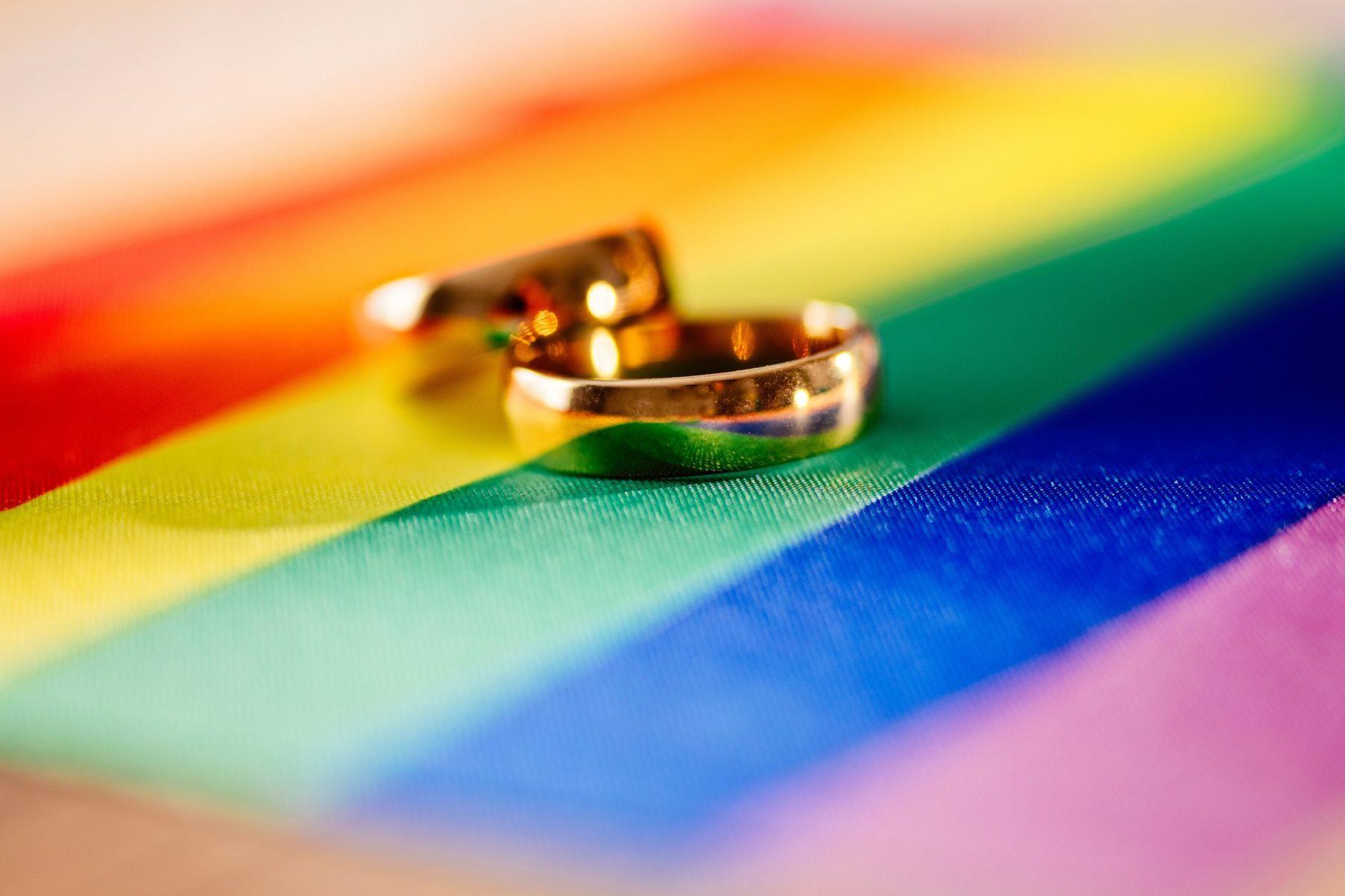 Photo symbole : deux alliances en or posées sur un drapeau arc-en-ciel