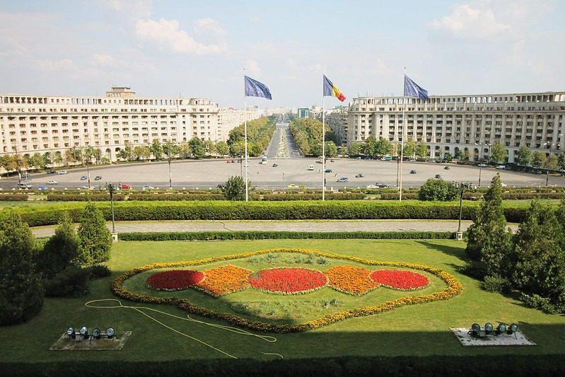 Vue depuis le Parlement roumain à Bucharest. Trois drapeaux flottent dont le drapeau roumain et celui de l'Union européenne