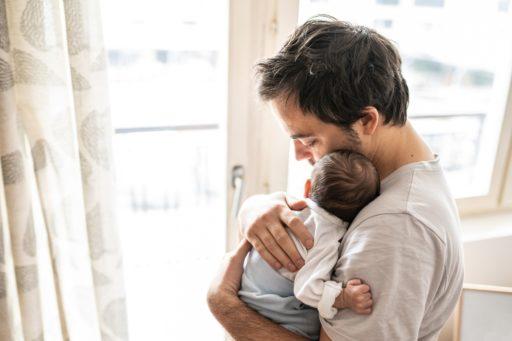 Un jeune papa tient son nouveau né contre lui