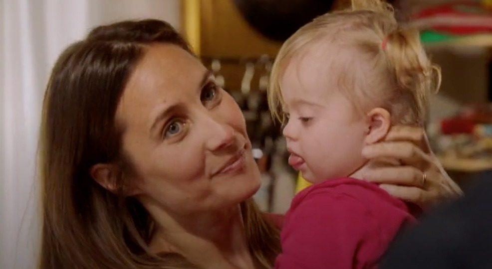 Image d'un téléfilm avec ne mère portant sans ses bras sa petite fille porteuse de trisomie 21