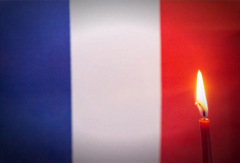 Bougie allumée sur le fond du drapeau de la France. Illustre le concept de deuil et de chagrin dans le pays