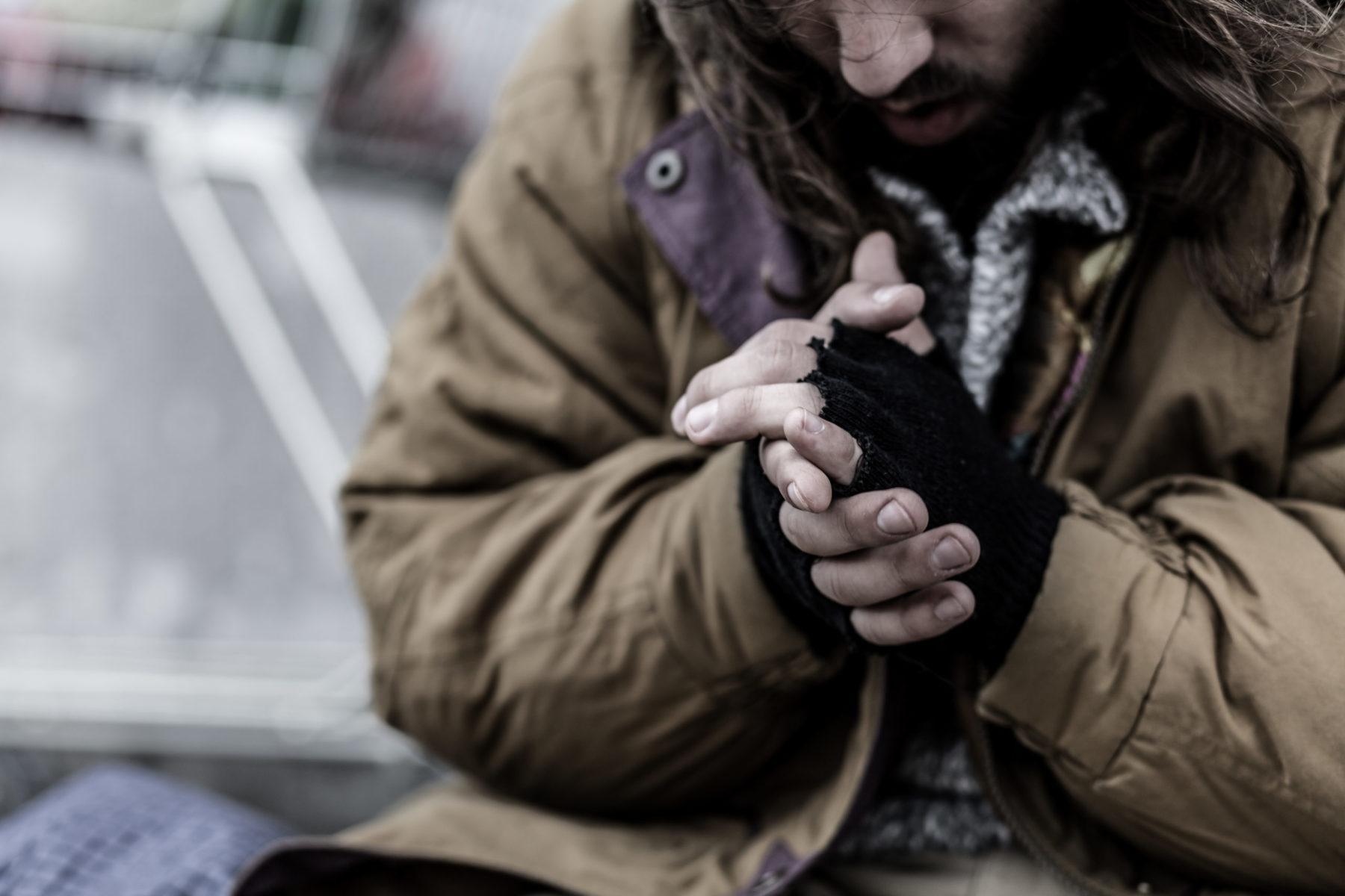 une personne sans abri à la rue les mains jointes a cause du froid et du manque