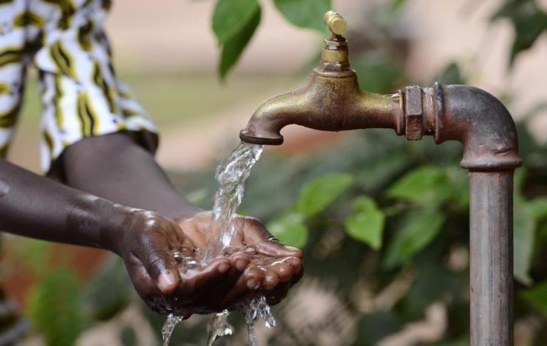 Les mains d'un enfant africain ouvertes en dessous d'un robinet. Photo d'illustration