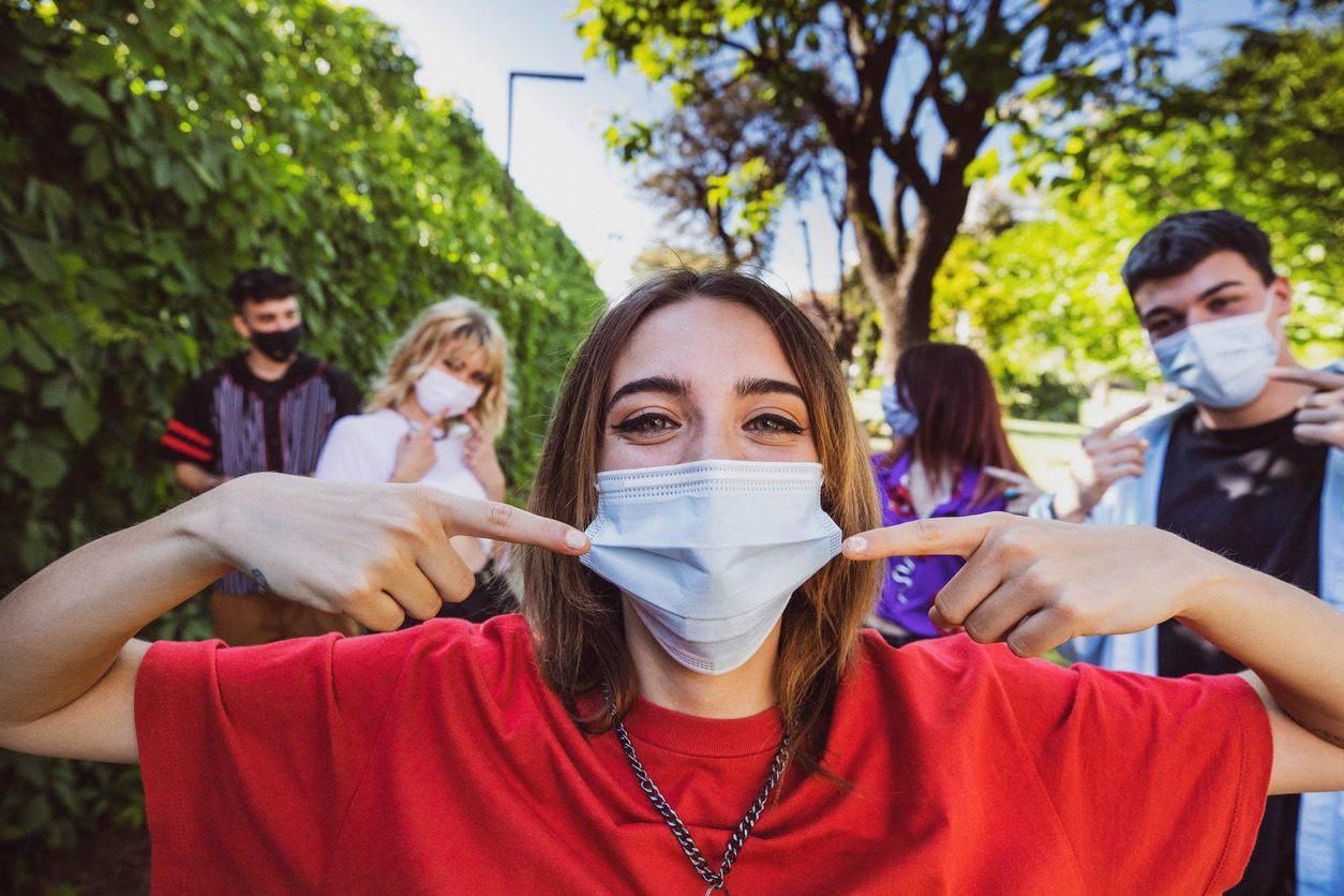 Un groupe d'adolescents posant en affichant leurs masques protecteurs