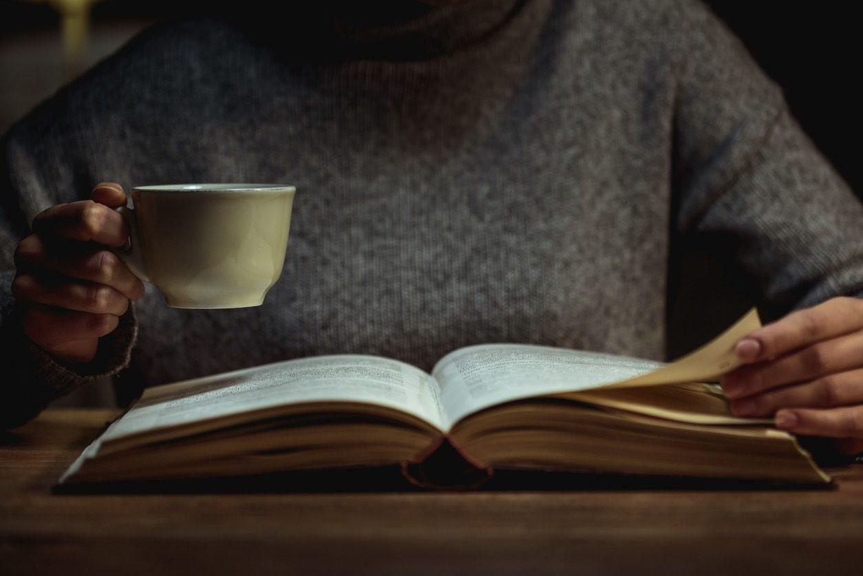 Une femme lisant sa Bible le soir, une tasse à la main