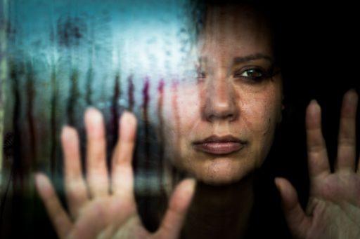 Une femme déprimée regardant la pluie tomber par la fenêtre pour illustrer la souffrance