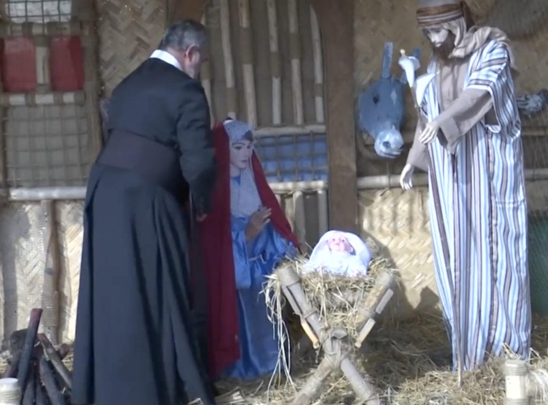 Prêtre irakien installant une crèche à Noel
