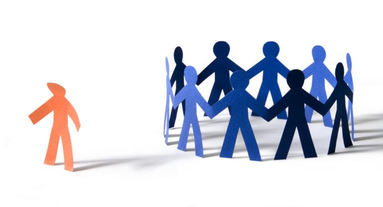 Image d'illustration. L'exclusion est douloureuse : le personnage en papier orange à une position abattue sur le côté d'un cercle de gens en papier bleu.
