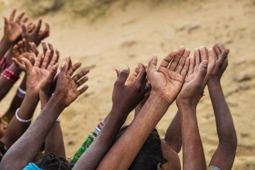 Des enfants pauvres indiens gardent leurs mains levées et demandent du soutien.