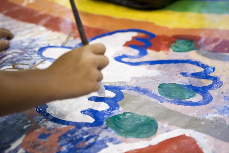 Un enfant peignant un colombe, symbole de paix.