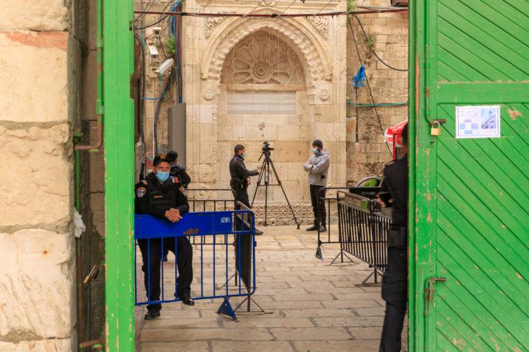 Des journalistes filmant derrière la porte Sha'ar ha Barzel - Bab Al-Hadid menant au mont du Temple, dans la vieille ville de Jérusalem, en Israël