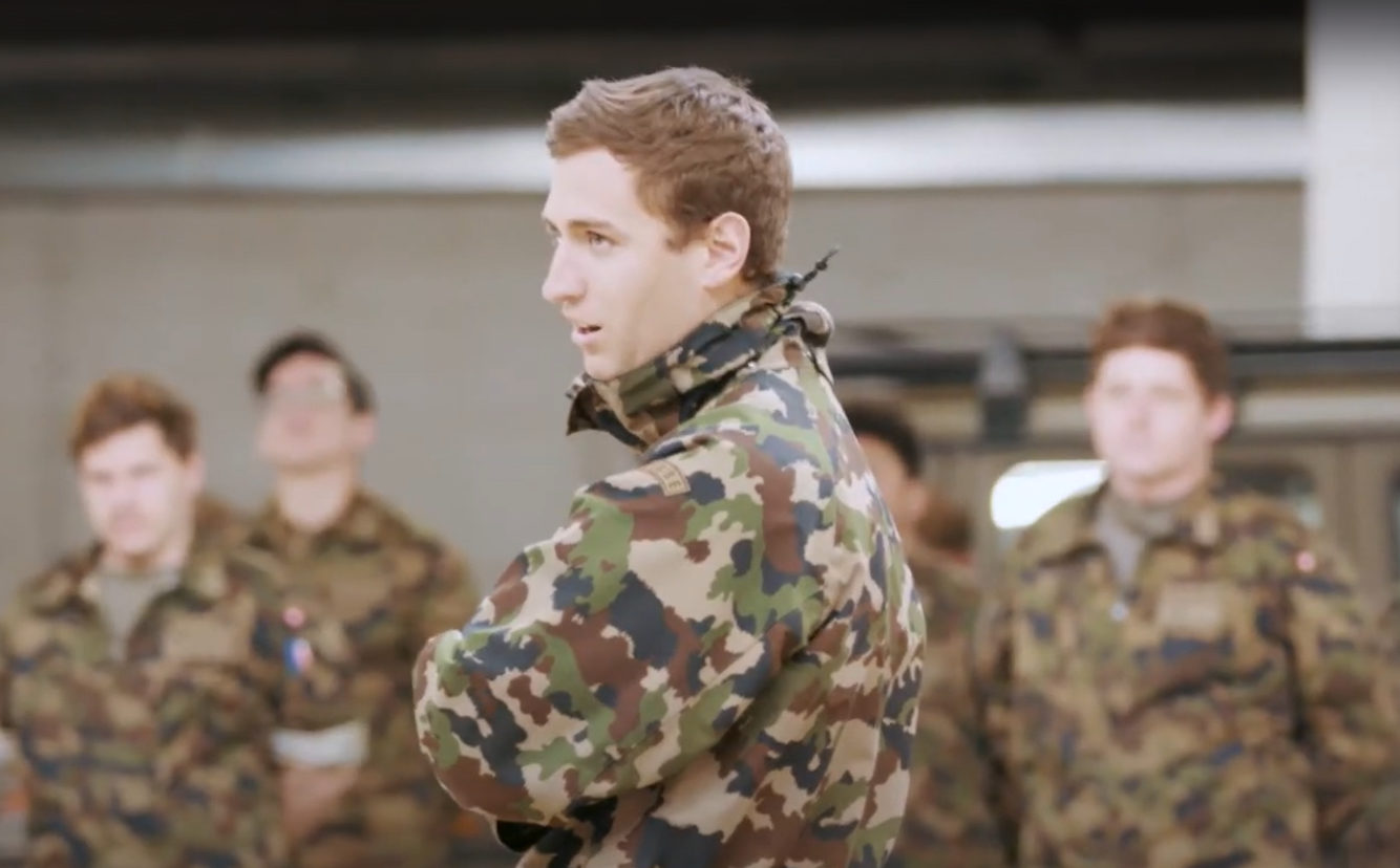 Un aumônier de l'armée suisse au milieu d'autres militaires