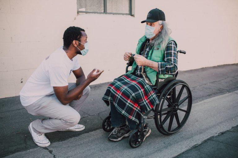 Un soignant se tient agenouillé devant une personne en fauteuil roulant