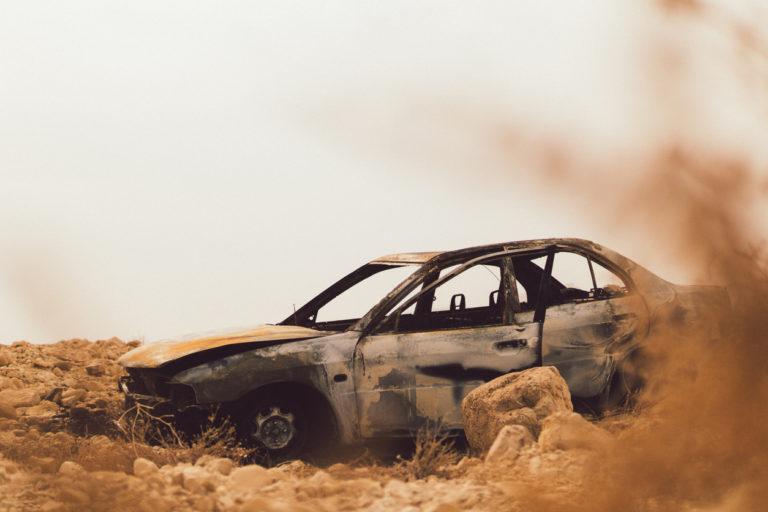 Voiture brûlée abandonnée dans le désert.