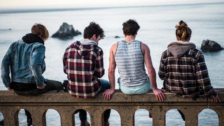 des adolescent assis sur une rambarde en bord de mer