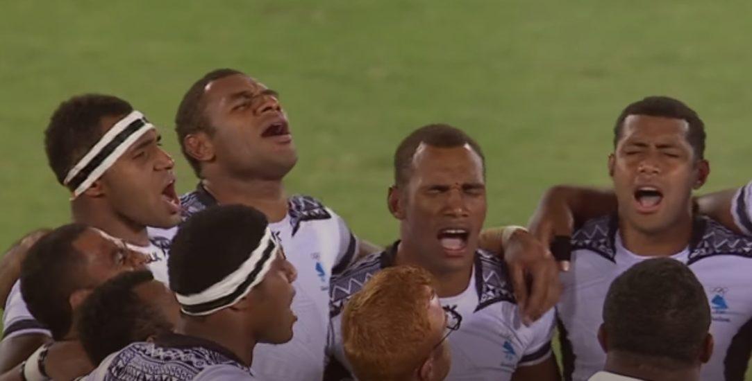 Groupe de rugby à 7 fidjien louant Dieu sur le terrain
