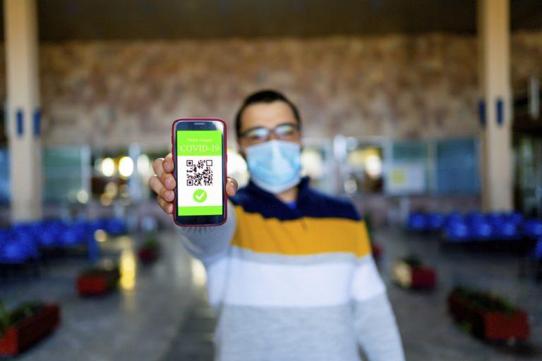 Jeune homme tenant un téléphone avec les détails de sa vaccination contre le covid-19