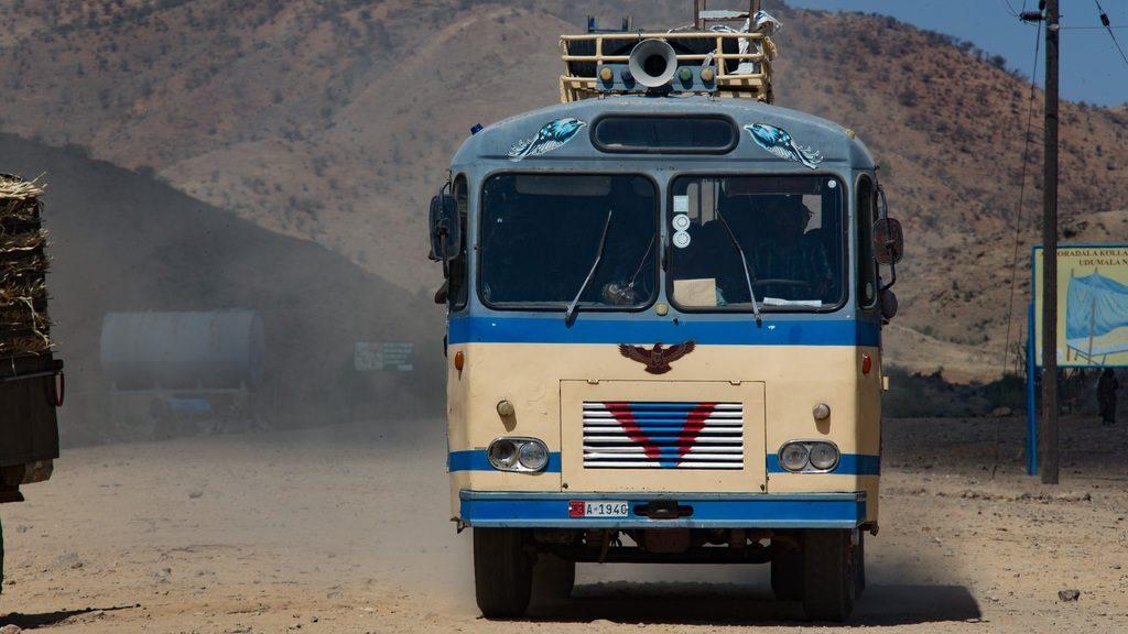 Bus de face sur une route sableuse