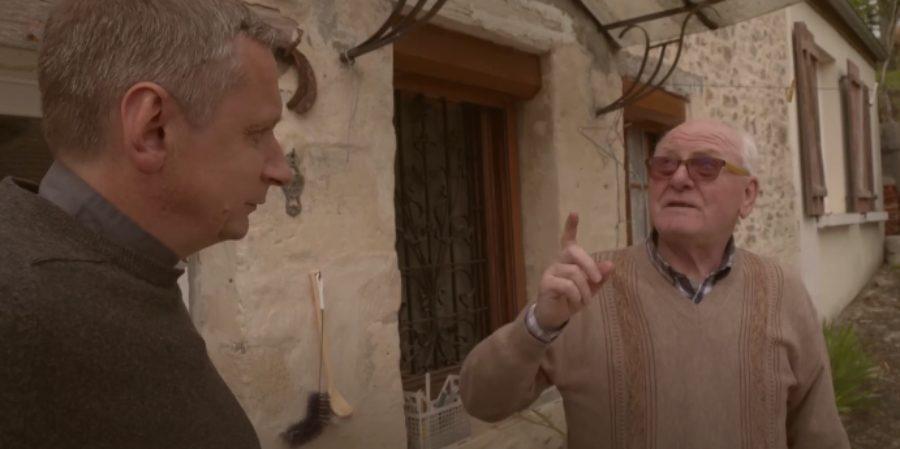 Un villageois parle en levant le doigt vers le ciel