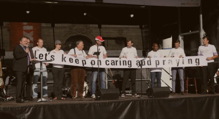 """Sur scène, déploiement d'une banderole """"Let's keep on caring and praying"""""""