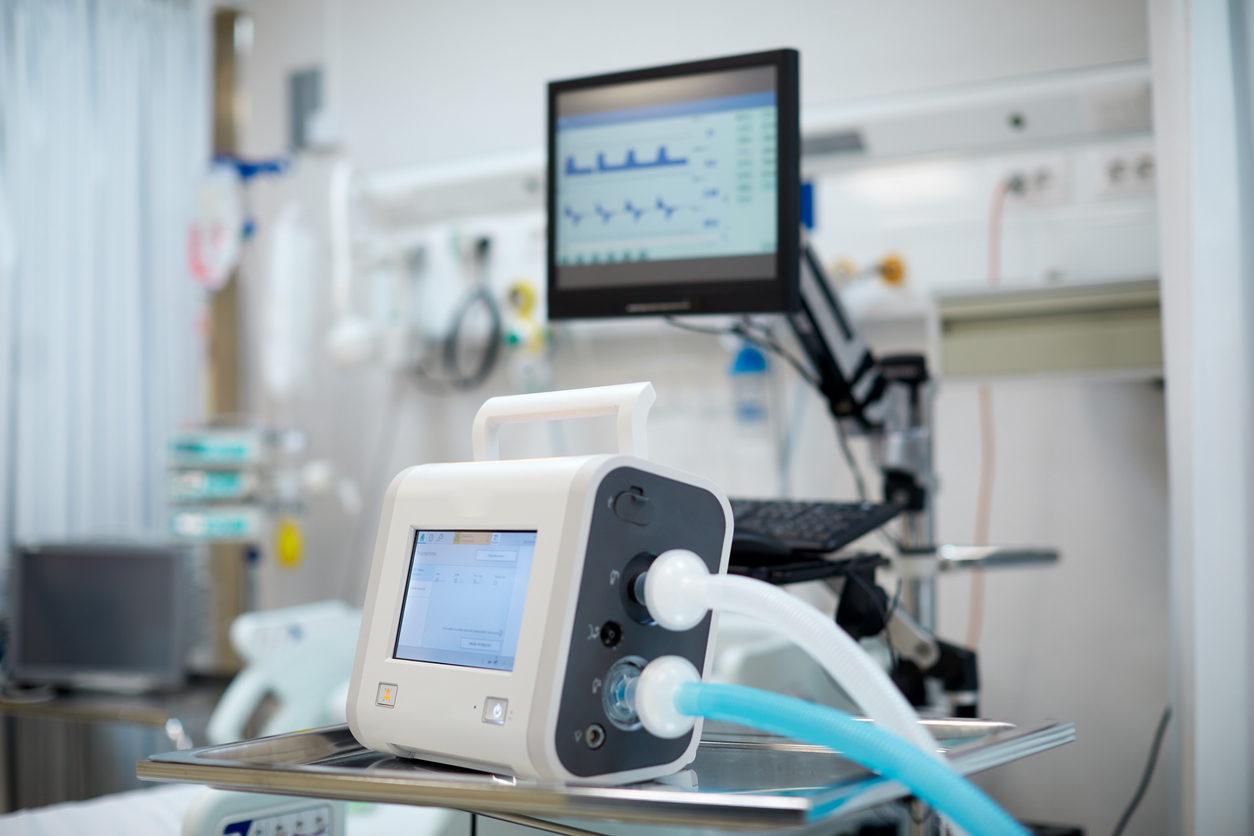Dans une chambre d'hôpital, un concentrateur d'oxygène et un moniteur de fréquence cardiaque