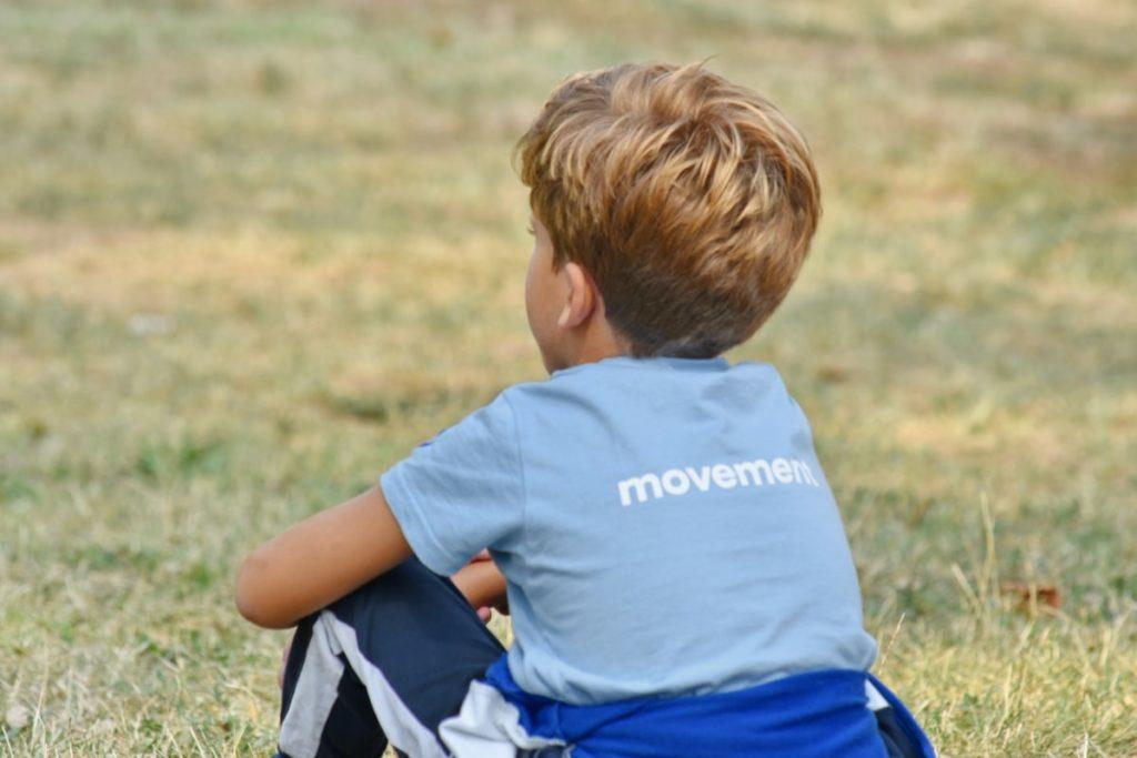 Un petit garçon blond est assis dans l'herbe, de dos
