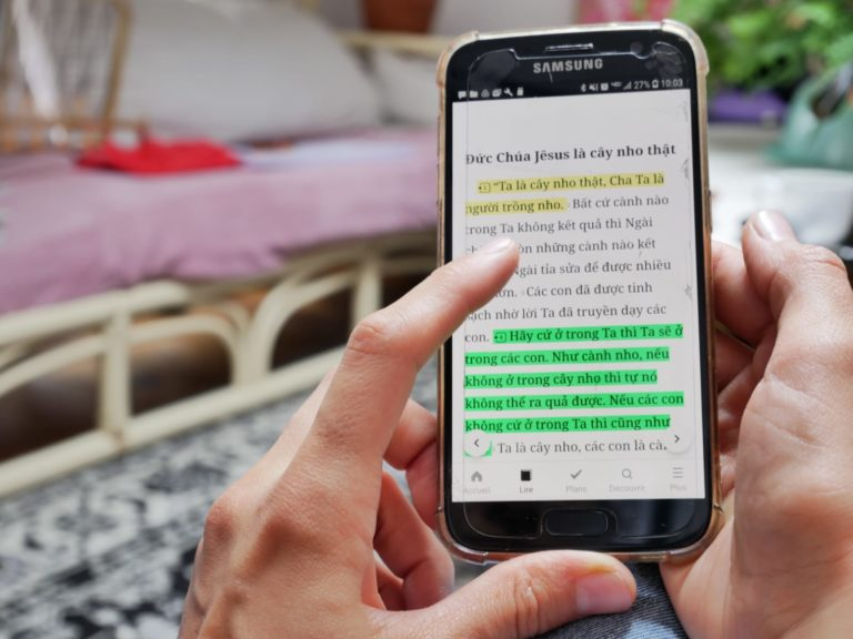 Des mains manipulent un smartphone où figure un texte biblique en langue vietnamienne)