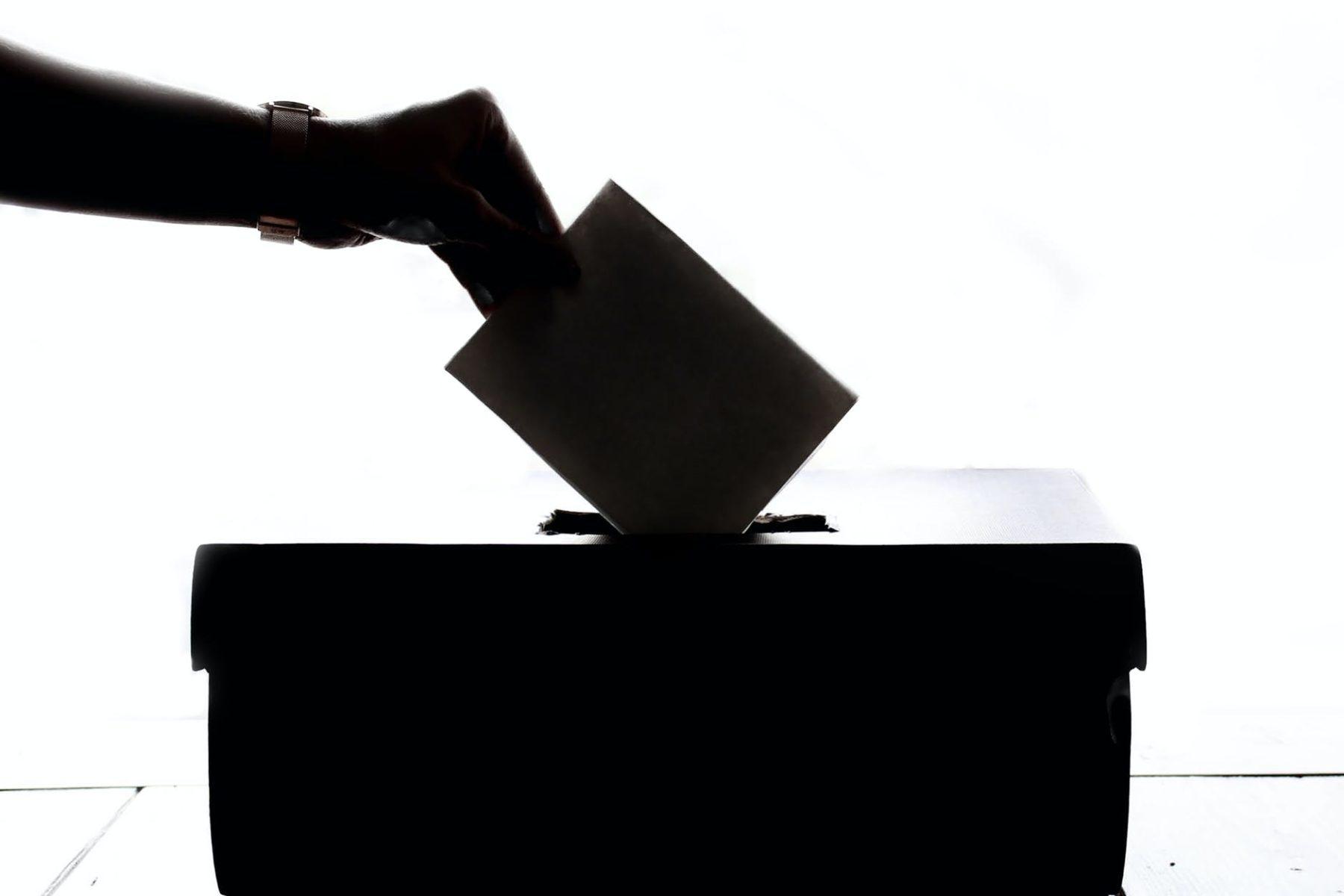Silhouette d'une main glissant une enveloppe dans une urne en noir sur fond blanc