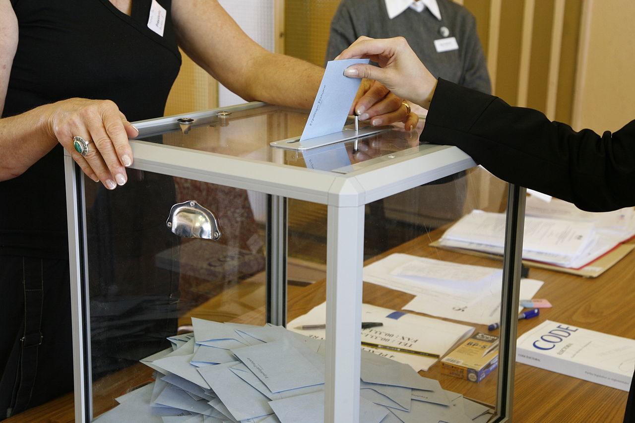 Quelqu'un insère une enveloppe dans une urne lors d'un vote