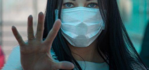 Une jeune femme portant un masque chirurgical fait signe de s'arrêter avec la main