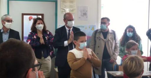Jean-Michel Blanquer et des élèves dans une classe, mains jointes