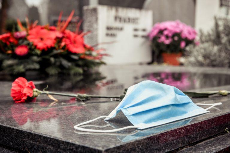 Un masque chirurgical est posé sur une tombe fleurie