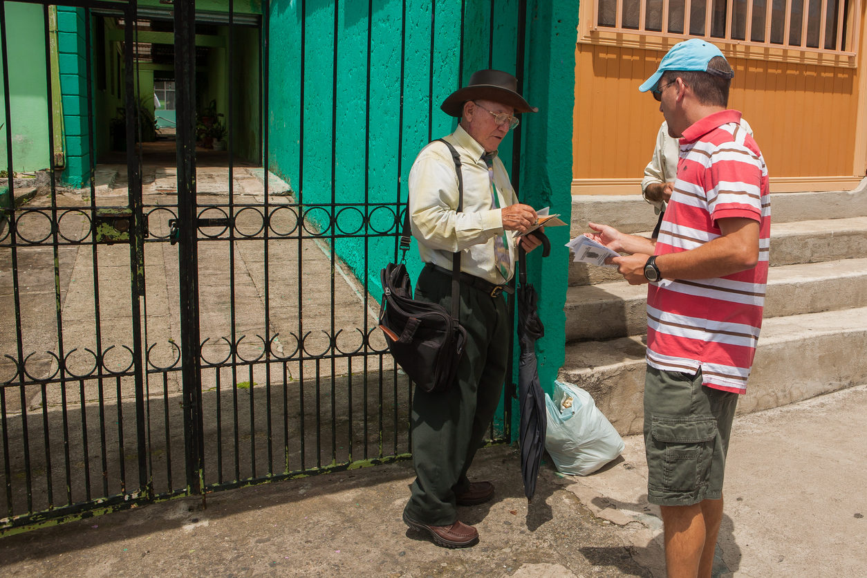 Un homme donne un tract à un autre dans la rue