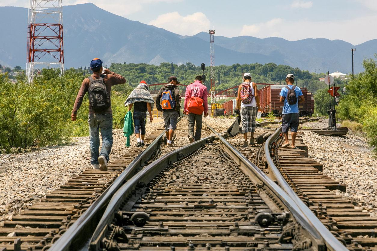 """Un groupe de migrants d'origine centraméricaine attend sur la ligne de chemin de fer pour monter à bord d'un train de conteneurs, connu sous le nom de """"La Bête"""", pour se rendre à la frontière des États-Unis et du Mexique, entre les États de Coahuila (Mexique) et du Texas (Etats-Unis)."""