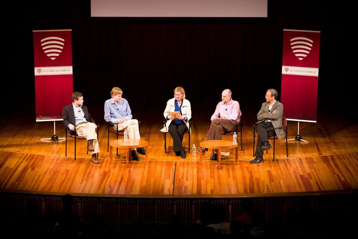 Quatre conférenciers sont assis sur une scène