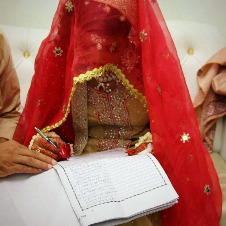 Une jeune mariée pakistanaise signe des documents de mariage. Elle est penchée en avant et couverte d'un voile rouge, on ne voit pas son visage