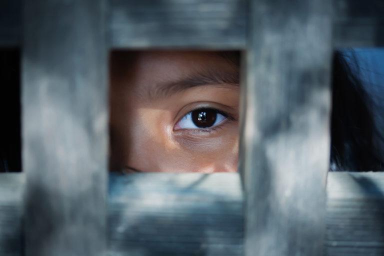 Le regard vide d'un œil d'enfant qui se tient derrière ce qui semble être un cadre en bois